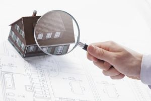 15284791 - concept image of a home inspection. a male hand holds a magnifying glass over a miniature house.